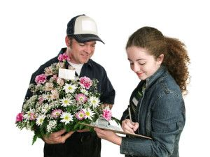 A teen girl signs for receipt of a bouquet of flowers.