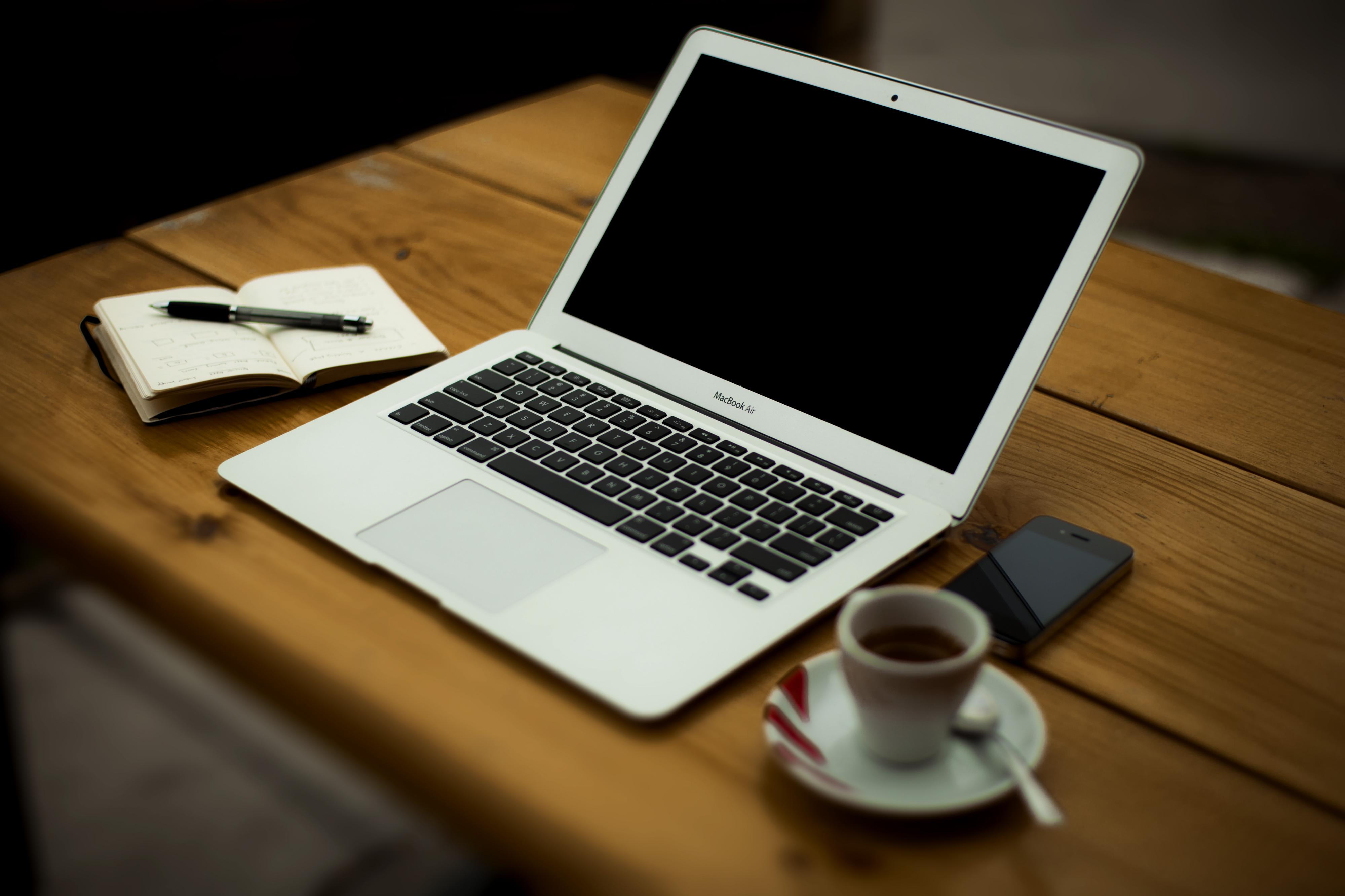 Picture of a laptop with a notebook and coffee cup on either side